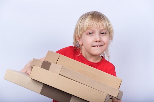 Śmieszna blond chłopiec mienia pizza boksuje na białym tle. dostawa posiłku do domu koncepcji.