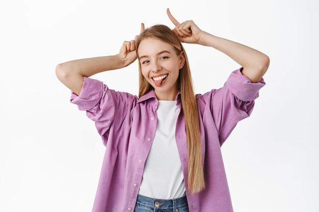 Śmieszna blond dziewczyna pokazuje gest diabła z rogów byka, pokazując język i uśmiechając się głupio, stojąc na białej ścianie