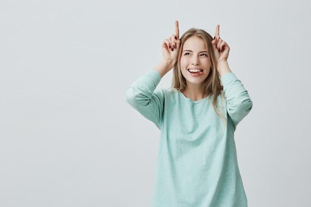 Śmieszna blondynki kobieta ono uśmiecha się szeroko trzyma palce nad głowa. gest rogi