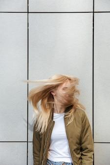 Śmieszna blondynki kobieta trząść jej włosy