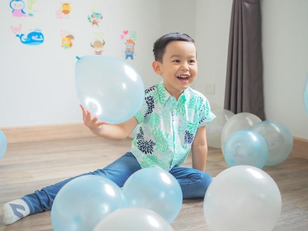 Śmieszna chłopiec bawić się z kolorowymi balonami