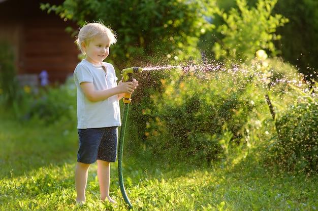 Śmieszna chłopiec bawić się z ogrodowym wężem elastycznym w pogodnym podwórku