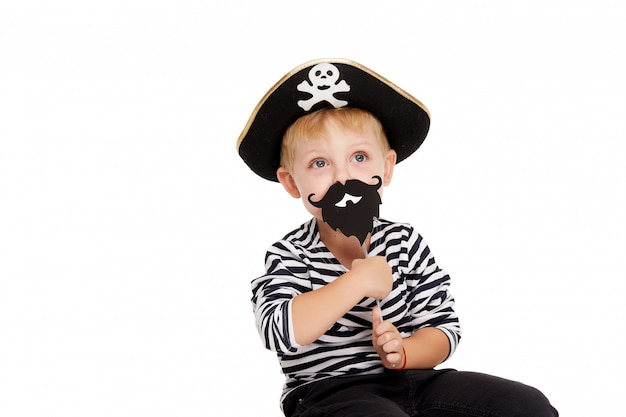 Śmieszna chłopiec stoi w karnawałowych kostiumach piraci z dużą banią na bielu