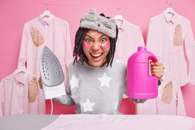Śmieszna ciemnoskóra pozytywna afroamerykanka ubrana w bieliznę nocną i opaskę na oczach trzyma żelazko parowe i detergenty pozuje przy desce do prasowania nakłada podkładki kolagenowe praca w domu wygląda szalenie