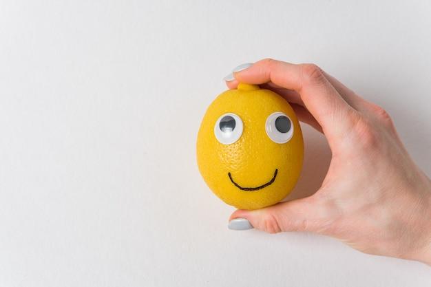 Śmieszna cytryna z oczami i uśmiechem na białym. kobiecej ręki trzymającej uśmiech cytryny.