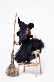 Śmieszna czarownica dziewczyna na białym tle z miotłą na białym tle