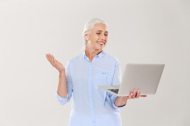 Śmieszna dojrzała kobieta używa laptop odizolowywającego nad bielem