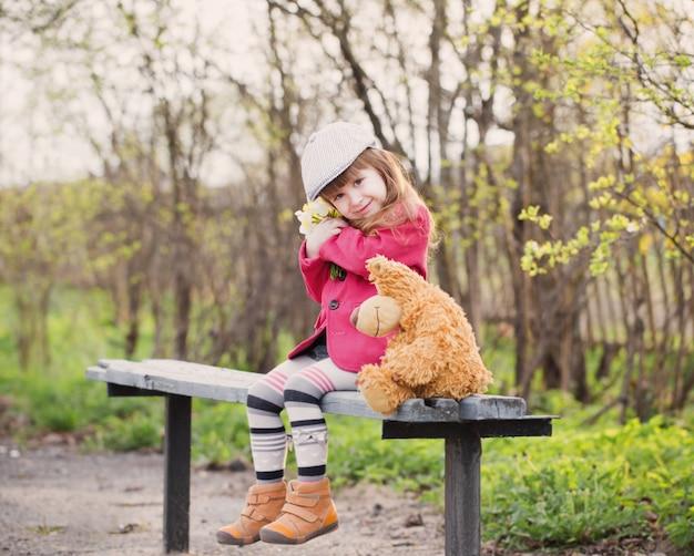 Śmieszna dziewczyna na ławce w wiosna parku