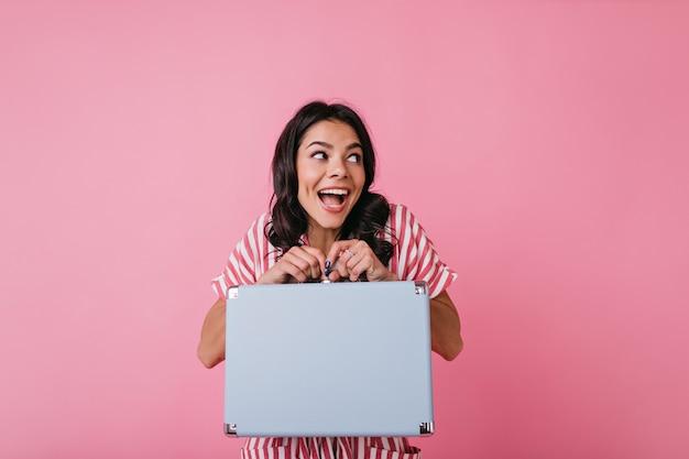 Śmieszna dziewczyna patrzy na bok z zainteresowaniem, mocno trzymając swoją torbę. modelka w różowej bluzce z białymi paskami pozuje.