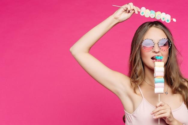 Śmieszna dziewczyna trzyma marshmallows na kiju pod głową, mieć zabawę.