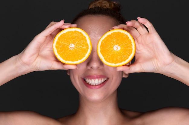 Śmieszna dziewczyna trzyma pomarańczowe plasterki