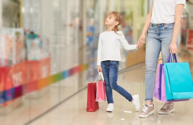 Śmieszna dziewczyna utrzymuje rękę matki w torby centrum handlowym
