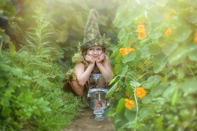 Śmieszna dziewczyna w gnomowym kapeluszu i kostiumu w zielonym ogródzie.