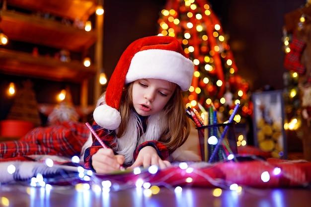 Śmieszna dziewczyna w santa hat pisze list do świętego mikołaja