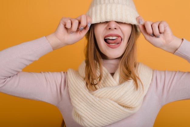 Śmieszna dziewczyna w szaliku naciągnęła na oczy kapelusz. na białym tle na szarym tle.