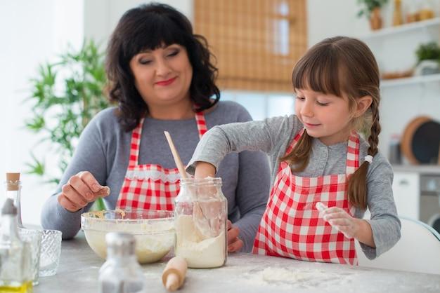 Śmieszna dziewczyna z warkoczykami wsypuje mąkę do ciasta. babcia pomaga wnuczce wspólnie gotować w kuchni.