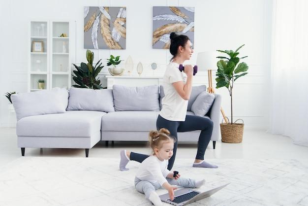 Śmieszna dziewczynka bawić się z laptopem podczas gdy jej sporty mamusia ma online joga trenuje w domu.