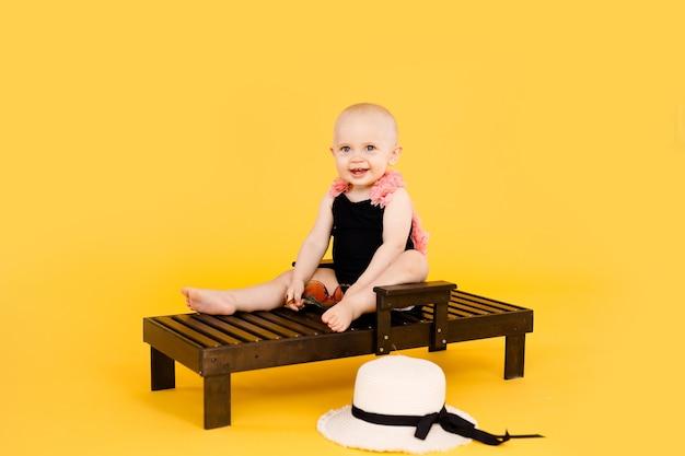 Śmieszna dziewczynka ubrana w czarno-różowy strój kąpielowy, duży kapelusz siedzi na drewnianym leżaku na białym tle na żółtym tle. koncepcja wakacji letnich