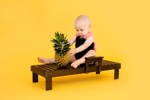 Śmieszna dziewczynka ubrana w czarno-różowy strój kąpielowy, duży kapelusz siedzi na drewnianym leżaku z ananasem na białym tle na żółtym tle. koncepcja wakacji letnich
