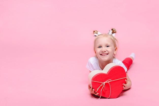 Śmieszna dziewczynka w białej koszulce i czerwonych spodniach z pudełkiem w kształcie serca na różowym tle. portret dziecka z miejscem na tekst.
