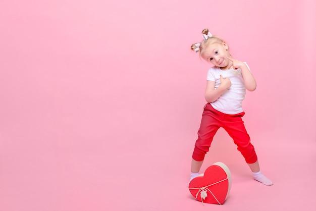 Śmieszna dziewczynka w białej koszulce i czerwonych spodniach z pudełkiem w kształcie serca na różowym tle.