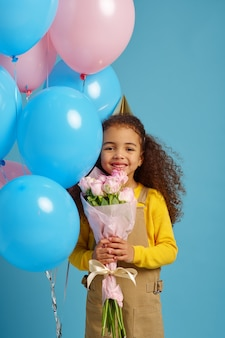 Śmieszna dziewczynka w czapce trzyma kilka kolorowych balonów i bukiet kwiatów, niebieskie tło. ładne dziecko dostało niespodziankę, imprezę lub przyjęcie urodzinowe
