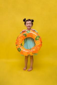Śmieszna dziewczynka w niebieskiej sukience trzyma nadmuchiwane koło na żółtym tle z kopią przestrzeni. orientacja pionowa. pełna długość