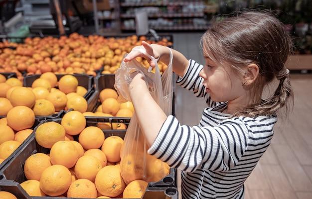Śmieszna dziewczynka w sklepie spożywczym wybiera pomarańcze do kupienia.