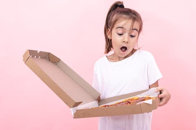 Śmieszna dziewczynka z pizzą w pudełku na różowym tle