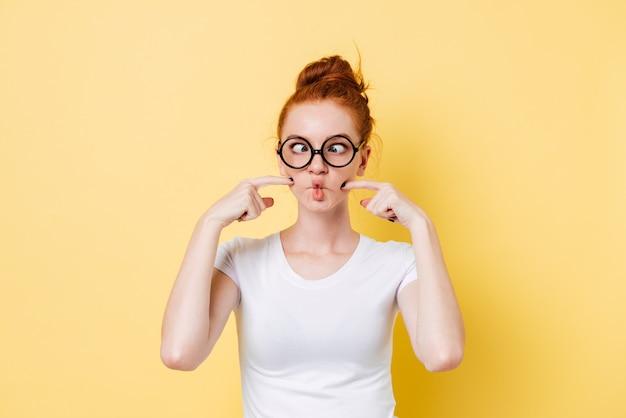 Śmieszna imbirowa kobieta w nadmuchiwanych policzkach okularów