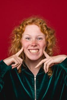 Śmieszna imbirowa młoda kobieta robi twarzy i toothy ono uśmiecha się