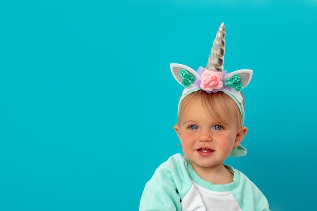 Śmieszna jednorożec mała dziewczynka na błękitnym tle