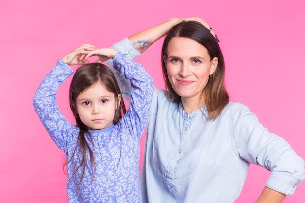 Śmieszna kobieta i dzieciak na różowej ścianie szczęśliwa rodzina bawić się w domu