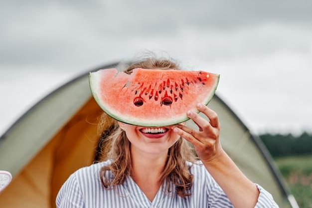 Śmieszna kobieta je arbuza na pinkinie. dziewczyna zamknęła oczy arbuzem, zaglądając do dziur