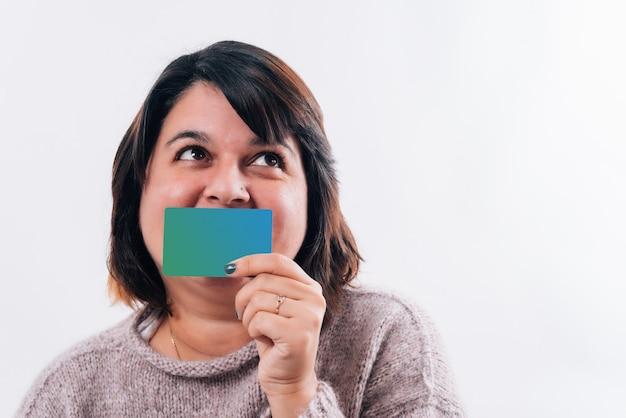 Śmieszna kobieta patrzy w bok, a uśmiech ukrywa karta kredytowa, która ją uszczęśliwia. koncepcja zakupów online lub w internecie. skopiuj miejsce