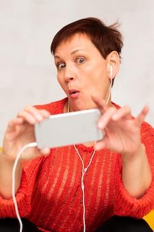 Śmieszna kobieta słucha muzykę i bierze selfie