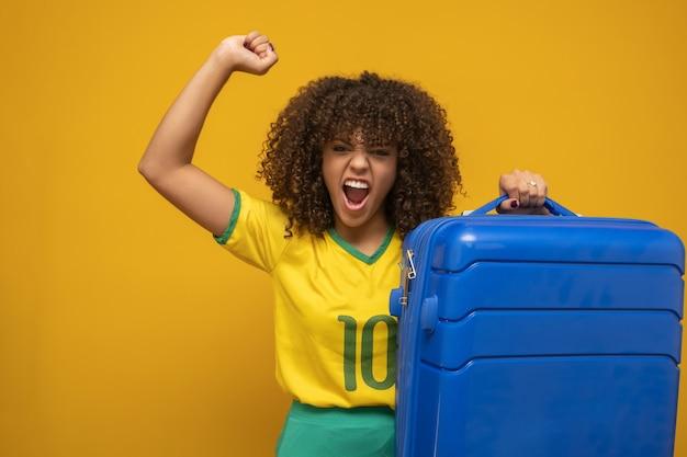 Śmieszna kobieta trzyma ciężką podróżną torbę