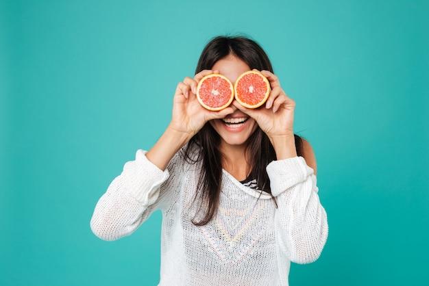 Śmieszna kobieta trzyma grapefruitowe połówki przed jej oczami