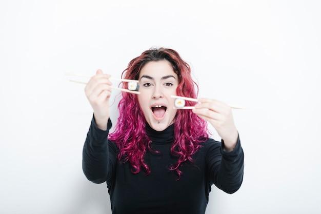 Śmieszna kobieta trzyma sushi z pałeczkami