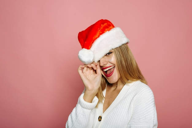 Śmieszna kobieta zakrywa jedno oko czapką świętego mikołaja i śmieje się. zalotna pani na różowym tle świętuje boże narodzenie i nowy rok.