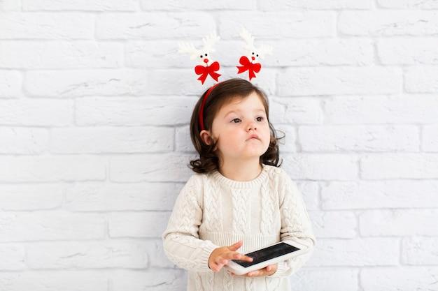 Śmieszna mała dziewczynka bawić się na telefonie