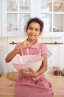 Śmieszna mała dziewczynka gotowanie ciasta, smaczne śniadanie. uśmiechnięte dziecko płci żeńskiej w kuchni rano. szczęśliwe dzieciństwo, młody kucharzu