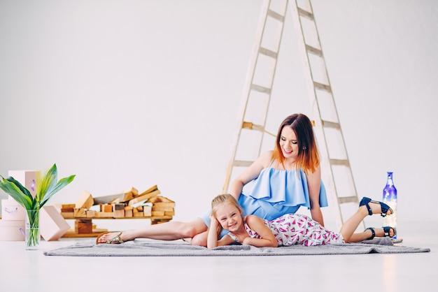 Śmieszna mała dziewczynka ma zabawę z jej mamą w białym dekorującym pokoju. puste miejsce, wolne miejsce na tekst.
