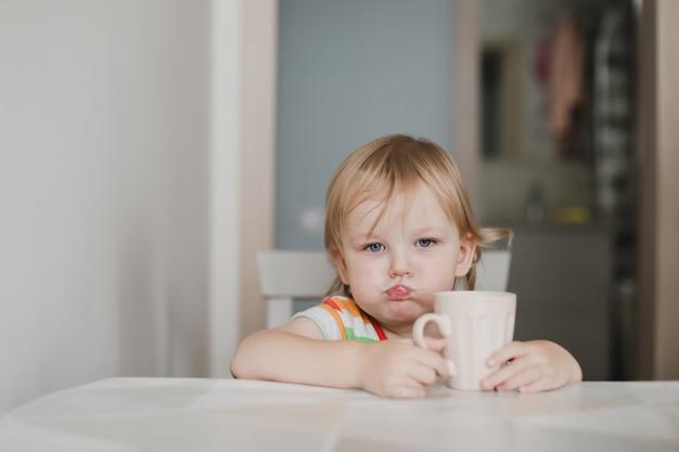 Śmieszna mała dziewczynka pije mleko siedząc w kuchni