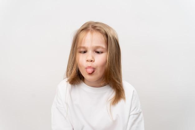 Śmieszna mała dziewczynka pokazuje język i grymasy na białym.