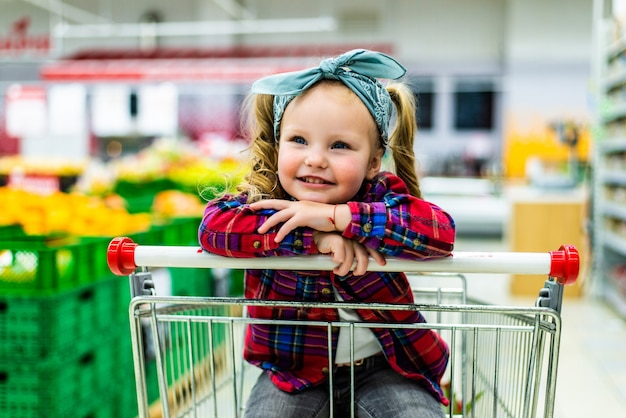 Śmieszna mała dziewczynka siedzi w wózku podczas rodzinnych zakupów w hipermarkecie