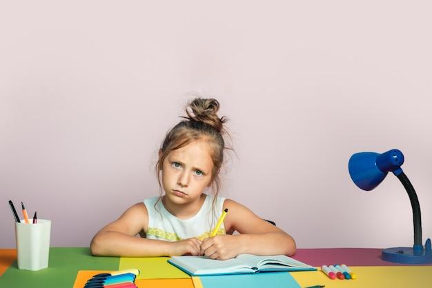 Śmieszna mała dziewczynka studia. profil małej dziewczynki pisze w domu. nieszczęśliwy rysunek dziecka w wieku szkolnym.
