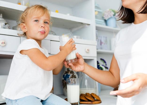 Śmieszna mała dziewczynka trzyma szkło mleko