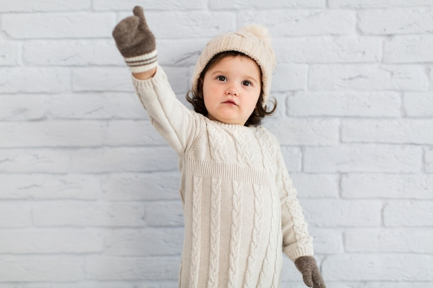 Śmieszna mała dziewczynka ubierająca zima