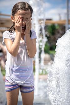 Śmieszna mała dziewczynka w fontannie, wśród rozprysków wody w upalny letni dzień.